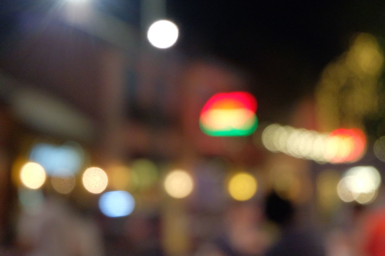 DEFOCUSED IMAGE OF ILLUMINATED LIGHTS AGAINST SKY