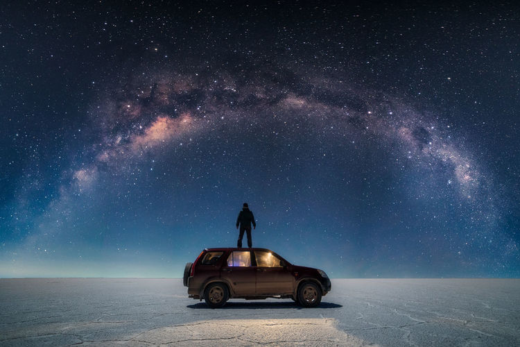 Man on car against sky at night