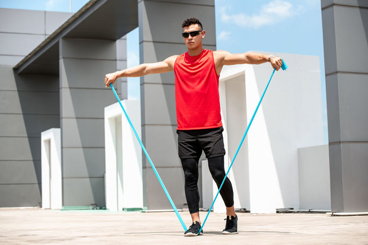 Full length of young man exercising with strap against built structure
