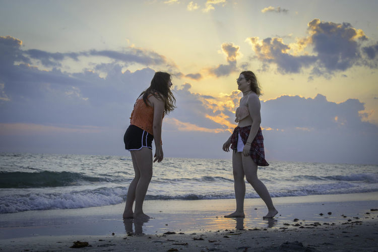 Rear view of friends walking on beach against sky during sunset