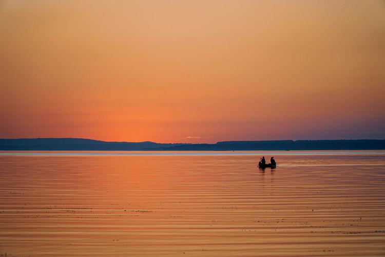 Silhouette people on boat in sea against orange sky