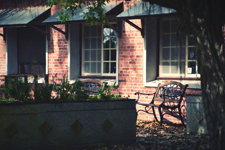 Empty bench by building during sunny day