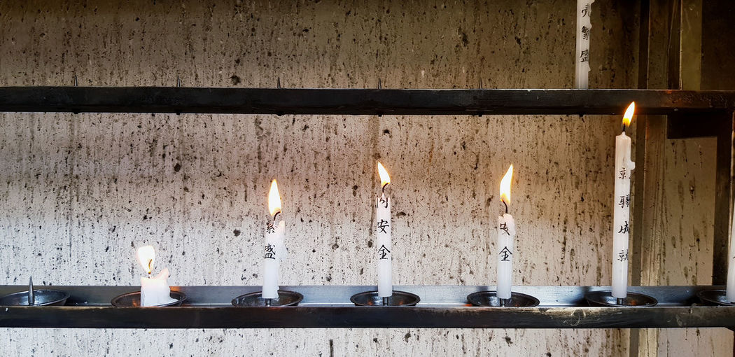 View of candles on table against wall