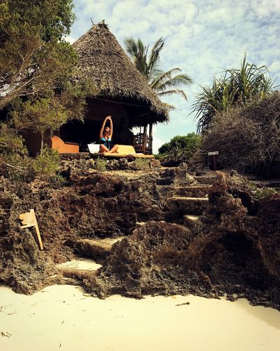 Thatched Roof Tree Sky Real People Outdoors Lifestyles Nature Tranquil Scene Day Landscape One Person Beauty In Nature White Dress Wealth Tourist Resort Wellbeing Vacations Serene People Leisure Activity Happiness Beachvilla Resort Africa Destination Tranquility