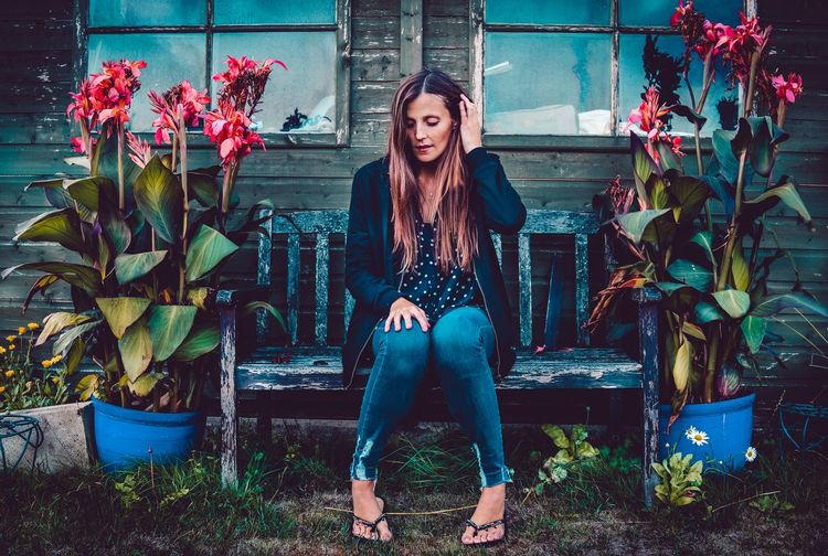 Portrait of beautiful young woman sitting by plants