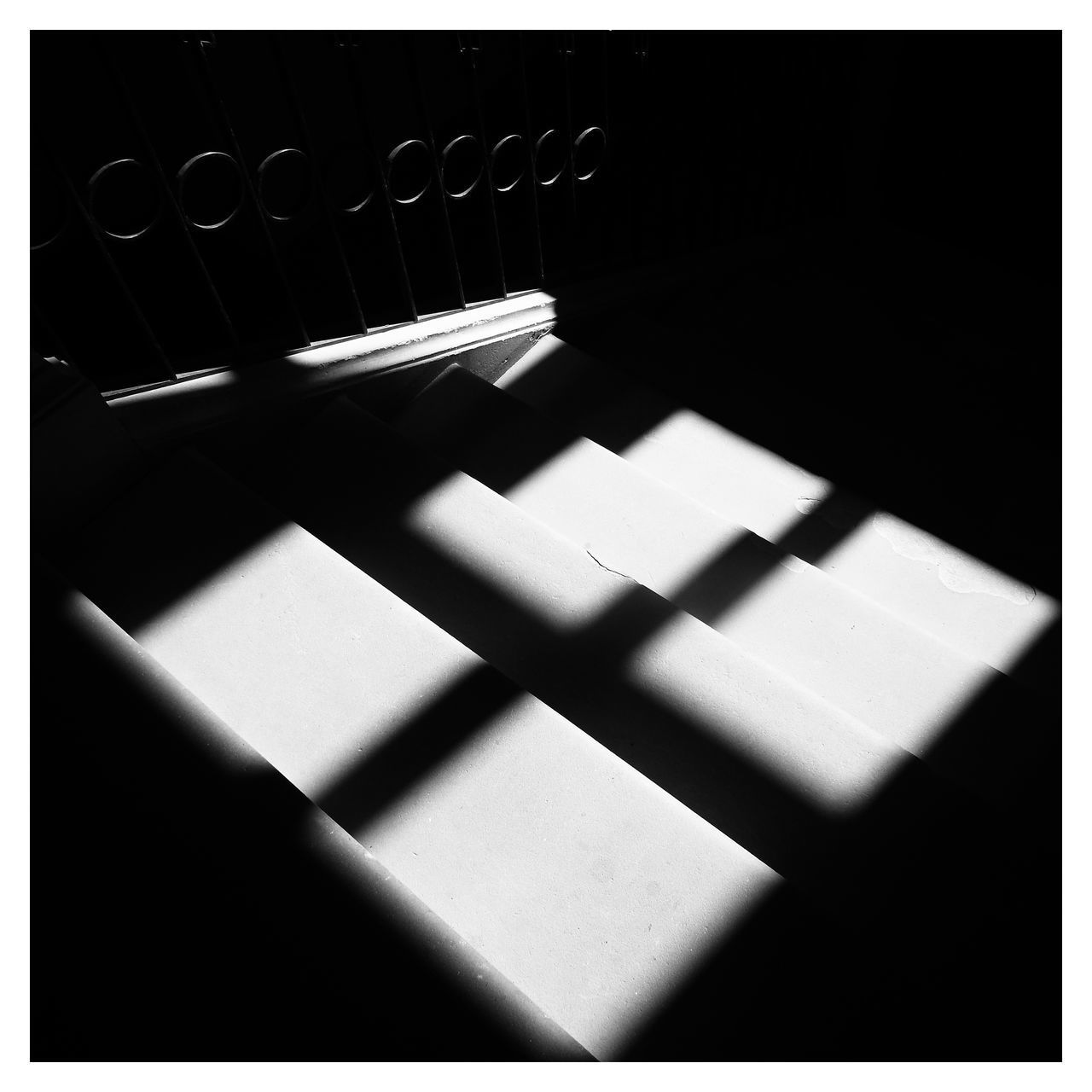 HIGH ANGLE VIEW OF SUNLIGHT FALLING ON FLOOR IN DARK ROOM