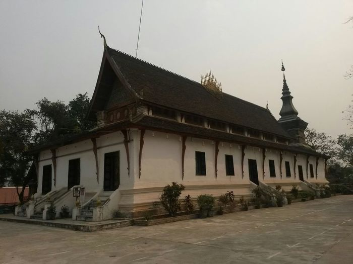 Luang Prabang City South East Asia Architecture Belief Building Building Exterior Built Structure Clear Sky Day History House Laos Nature No People Outdoors Place Of Worship Plant Religion Residential District Sky Spire  Spirituality Temple The Past Tree