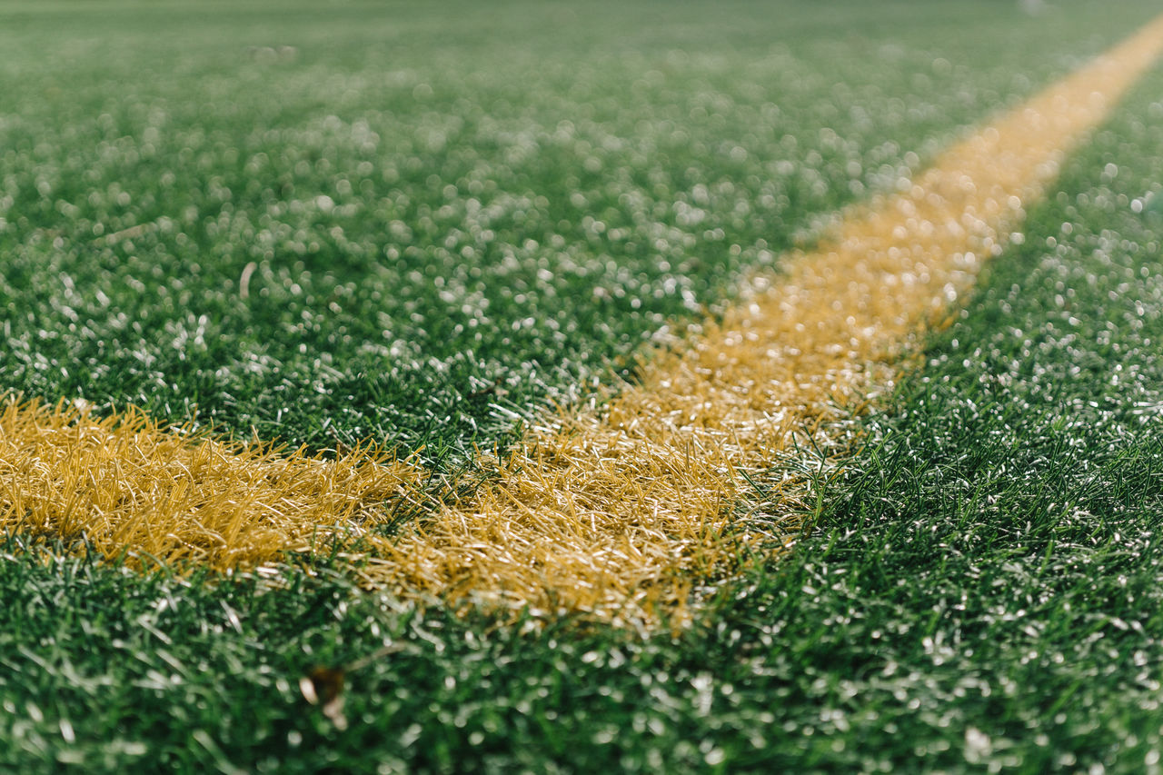 Close-up of yellow yard line on soccer field