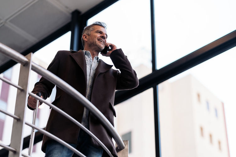 Man looking at camera while standing on railing