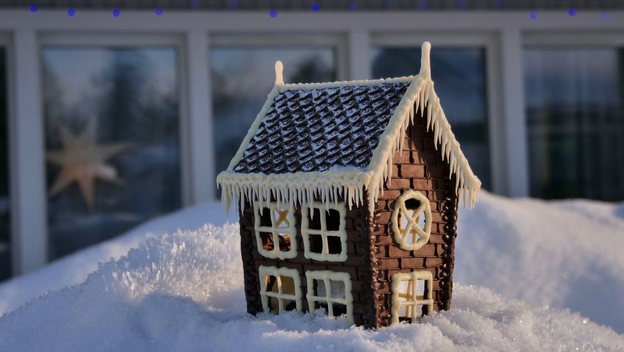 Close-up of snow covered house on field against building