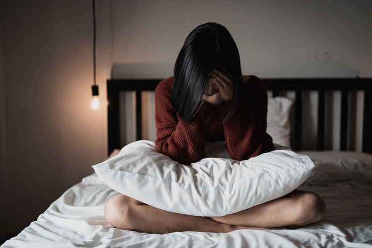 Sad young woman sitting on bed at home