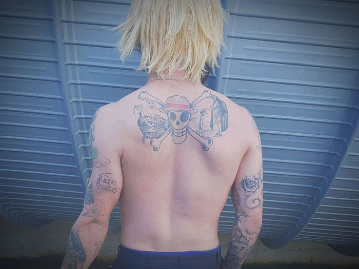 Rear View Of Shirtless Tattooed Man Standing By Blue Structure