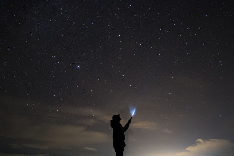 Silhouette man holding illuminated flashlight while standing against star field at night