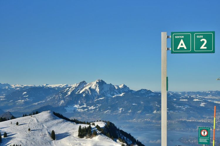 Road sign on snow covered mountain against blue sky