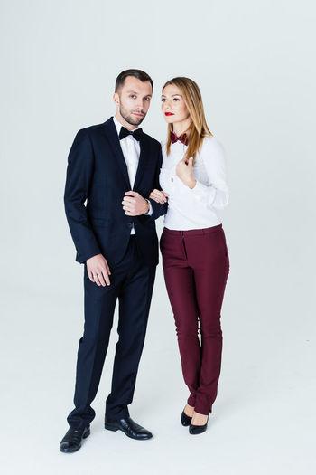 Full length of elegant couple standing against blue background