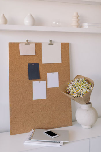Flower vase with smart phone and book on table by wall at home