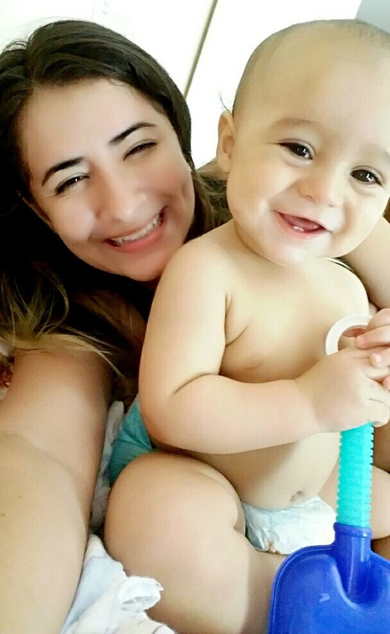 smiling, two people, togetherness, looking at camera, happiness, sitting, baby, childhood, portrait, front view, indoors, cute, real people, young women, young adult, bonding, full length, day, close-up