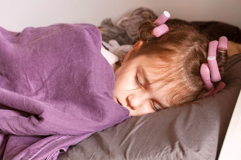 Close-up of girl sleeping on bed at home