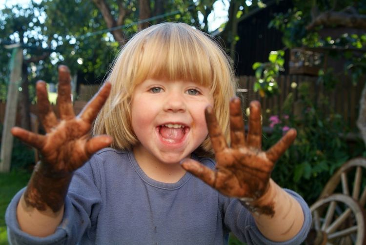 Portrait of playful girl showing messy hands while standing at backyard