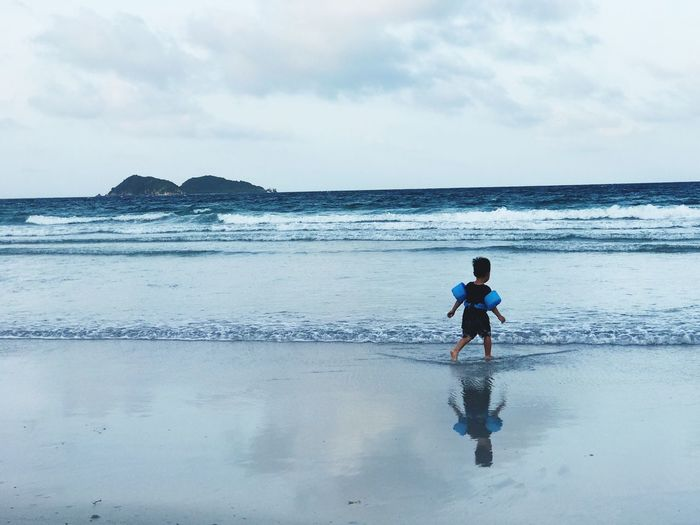 Rear View Of Boy Wearing Water Wings While Walking On Shore At Beach Against Sky