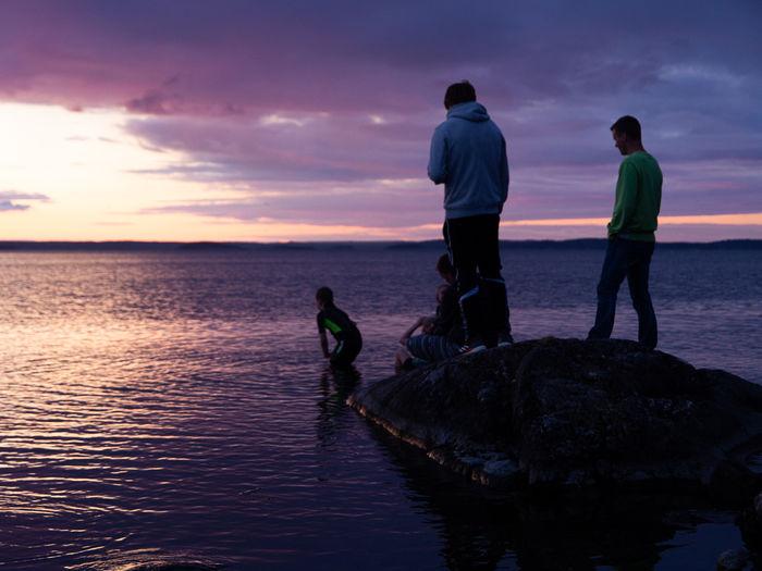 Men standing on rock by sea against sky