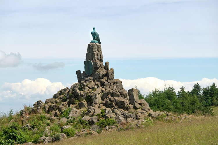 Statue against rock formation against sky