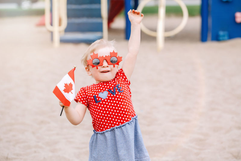 Portrait of cute girl wearing sunglasses while holding flag on sand