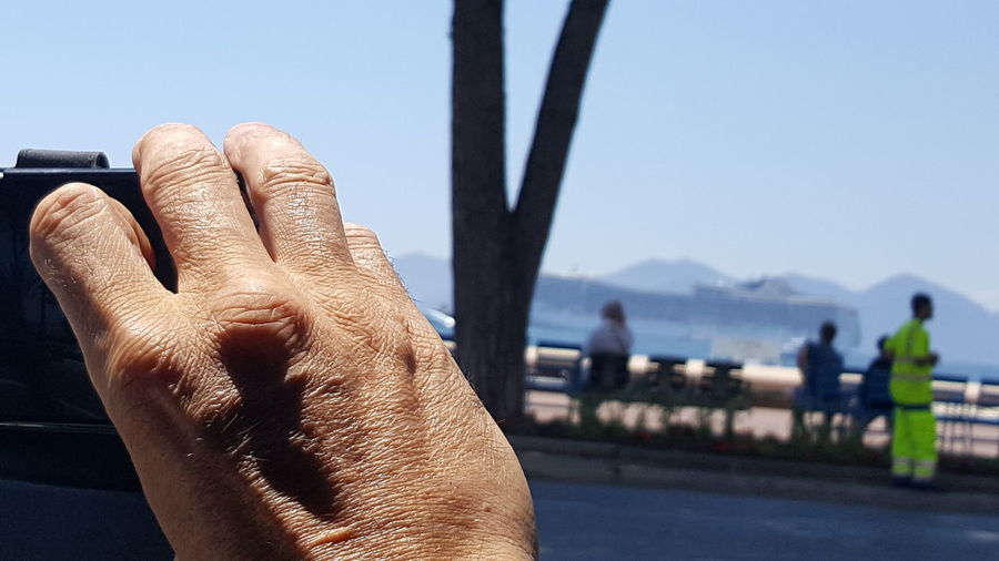 Close-up of man hand against sky