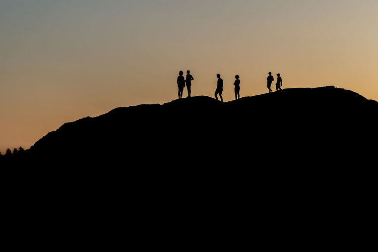 Silhouette of a group of people against sunset