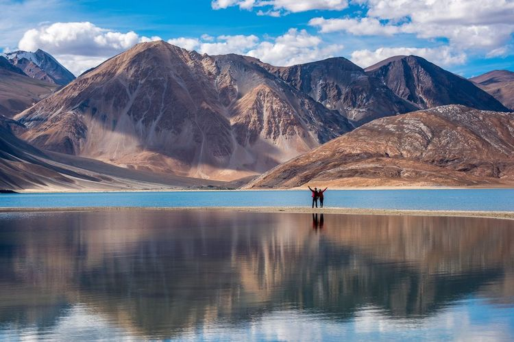 Man and woman standing at lake against mountains