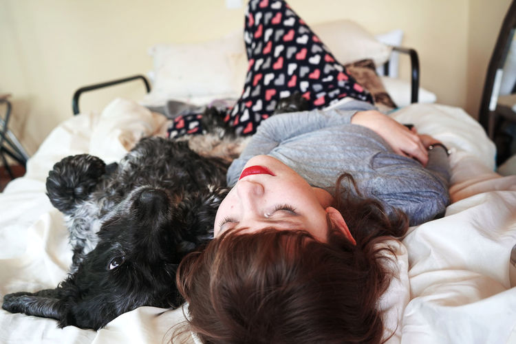 Woman with dog sleeping on bed at home