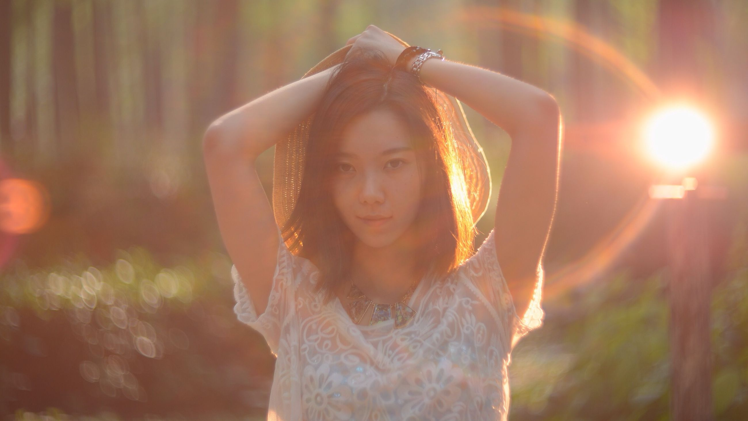 lifestyles, person, leisure activity, portrait, looking at camera, young adult, happiness, young women, front view, smiling, casual clothing, standing, focus on foreground, sunlight, lens flare, headshot, enjoyment, outdoors