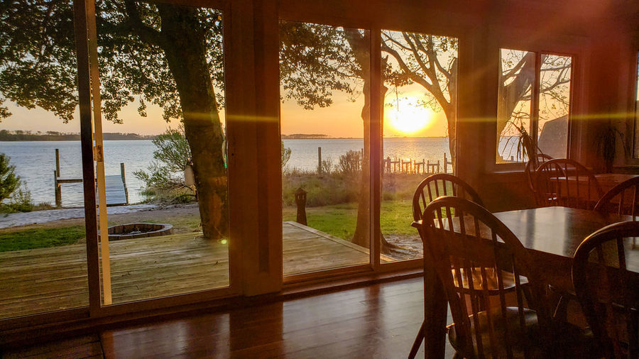 Sunset by the lake interior shot. interior Interior Views Interior Water Sea Tree Window Sunlight Curtain Sky Architecture Looking Through Window Calm Sunset Horizon Over Water Waterfront Balcony Sun Seascape Shore Ocean Silhouette Sunbeam Idyllic Tranquility Tranquil Scene Shining Countryside Sliding Door Streaming Non-urban Scene Lakeside