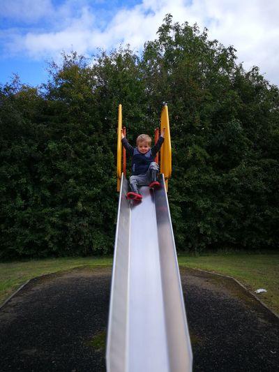 Full length of boy on slide at park