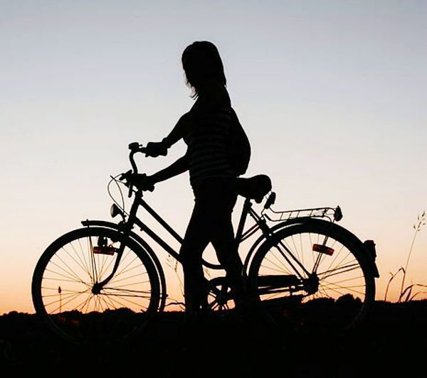 Silhouette of woman with bicycle against sky