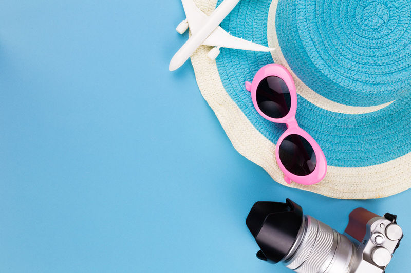 High angle view of sunglasses with camera and hat over blue background