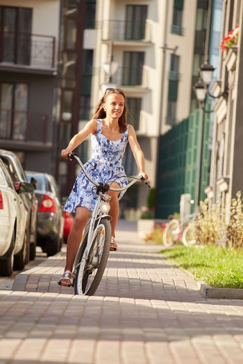 Cute woman cyclist in blue dress moves on bicycle in city smiling