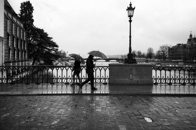 People with umbrella walking on promenade against sky during rainy sea season