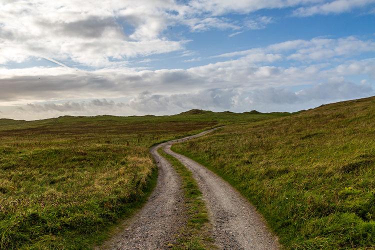 Road passing through landscape against sky