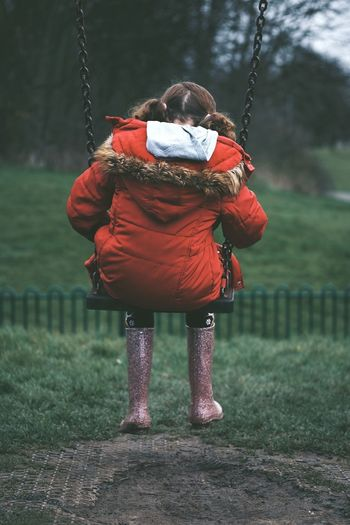 Rear View Of Girl Wearing Warm Clothing Sitting On Swing