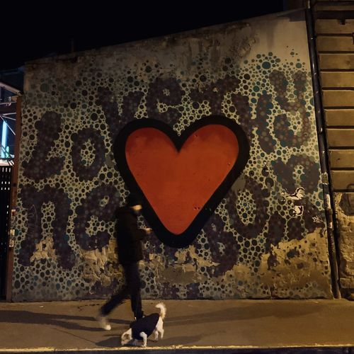 Midsection of woman standing by heart shape on wall