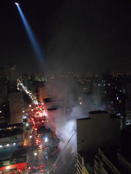 Inner City Calamity in downtown São Paulo at Largo do Paissandú; 3 am May 1, 2018. The abandoned former Federal Police steel and glass skyscraper, which had been invaded by street people, imploded this early morning and the neighboring building has caught on fire as well. This photo captures the effect of a patrol helicopter with its spotlight on in the night sky about 4 am, May 1, 2018. 4 Am City City Life Destruction Helicopter Largo Do Paissandu May 1, 2018 Night Photography Susan A. Case Sabir Unretouched Photography About 4 Am Building Fire Building Implosion Burning Building Controlled Chaos Dangerous Situation Downtown São Paulo Helicopter Spotlight High Angle View Implosion Responsiveness Smoke - Physical Structure Unexpected Event Urban Photography Urban Strife