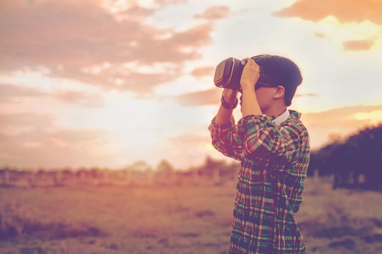 Boy photographing on field against sky during sunset
