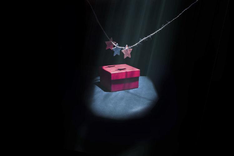 Red umbrella in box against black background