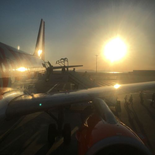 Sun Lens Flare Transportation Sunset Sunbeam Mode Of Transport Airplane Air Vehicle Sunlight Sky Travel Journey Airport No People Illuminated Outdoors Nature Runway Low Section Commercial Airplane