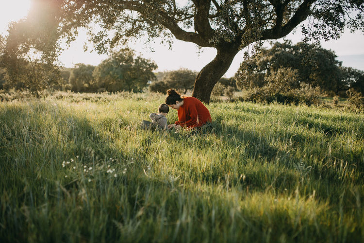 Mother and son crouching on grass at field