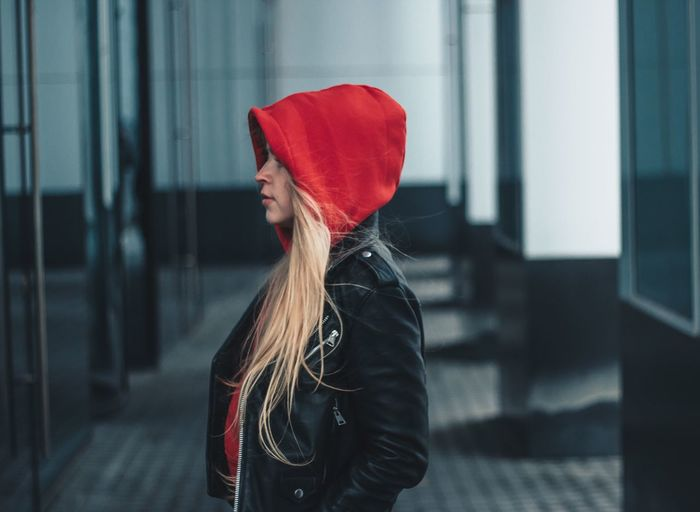 Young woman wearing hood while standing by building