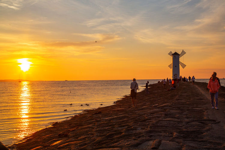 Baltic Sea Stawa Mlyny Beach Beauty In Nature Cloud - Sky Group Of People Horizon Horizon Over Water Land Lifestyles Nature Orange Color Outdoors Real People Scenics - Nature Sea Sky Sun Sunset Tranquility Water Women