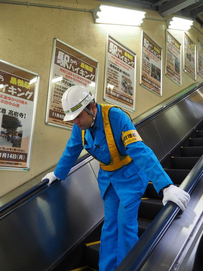Adult Blue Day Escalator Examining Headwear Indoors  Manual Worker Men Occupation Occupational Safety And Health People Protection Protective Glove Protective Mask - Workwear Protective Workwear Safety Skill  Standing Technician Uniform Working