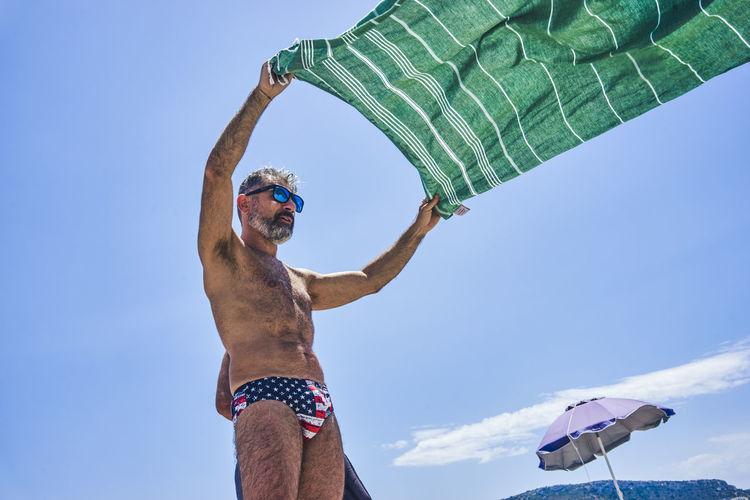Man in costume shaking a beach towel on a sunny beach in sardinia